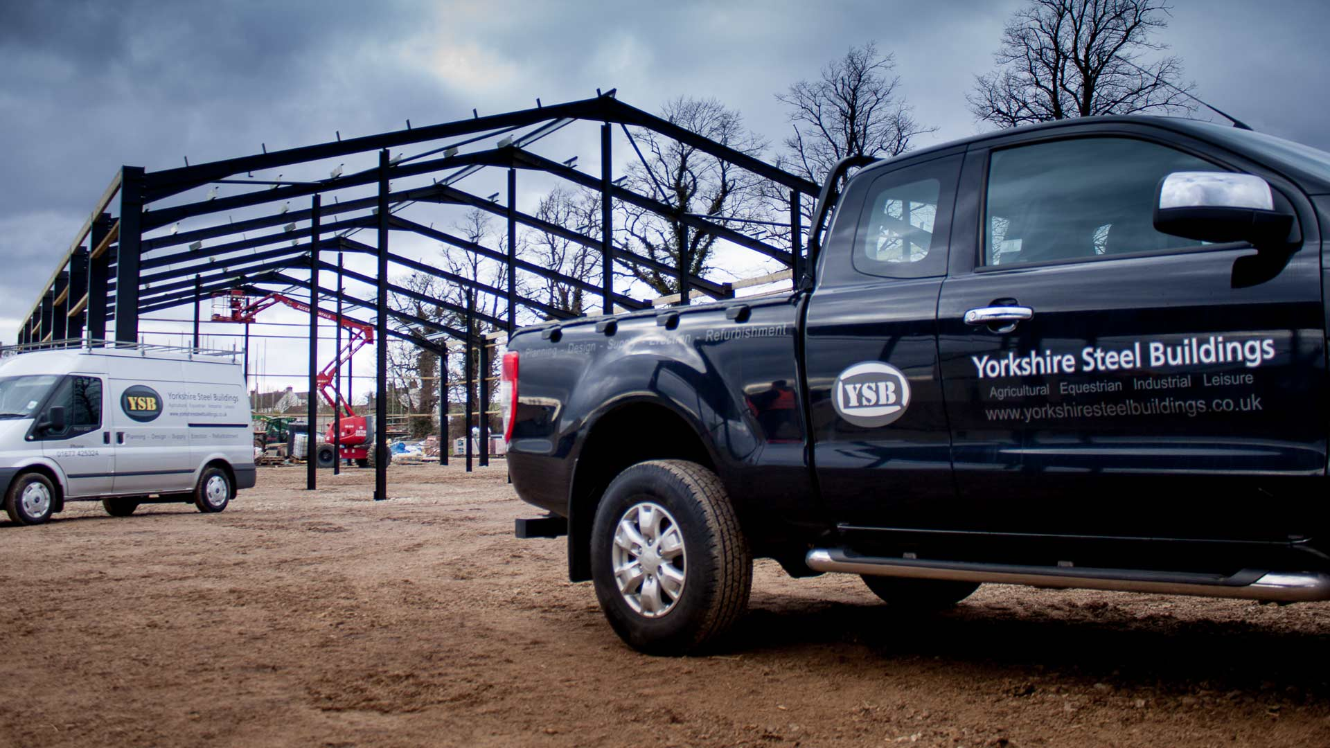 The YSB works vehicles parked neatly in front of a new steel frame farm building